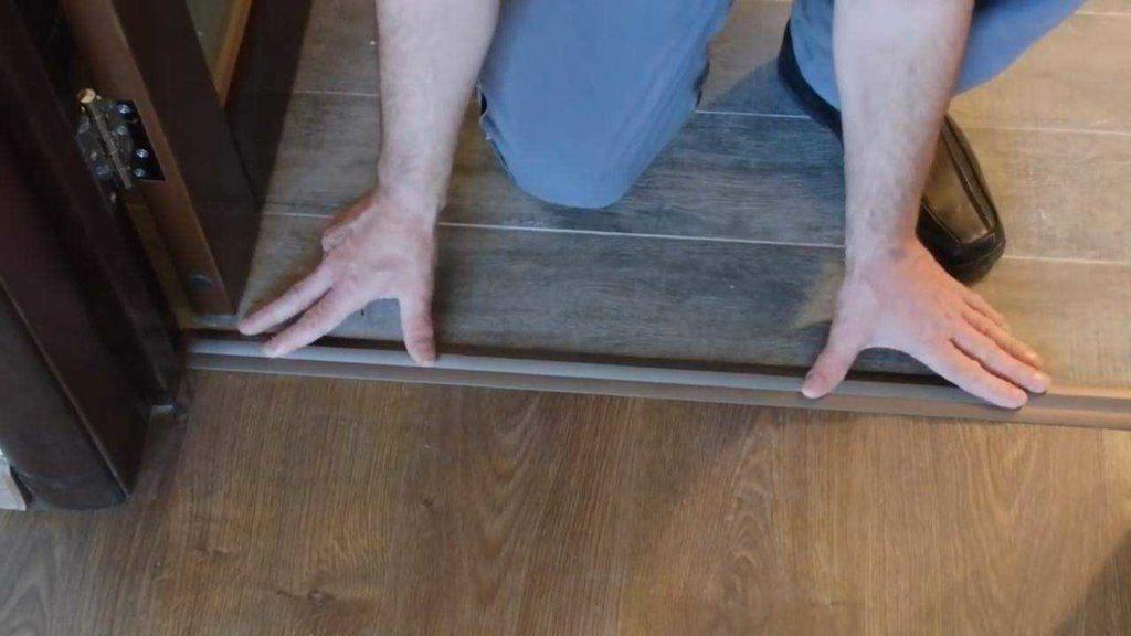 Стыковка плитки и ламината в дверном проеме при помощи порожка выглядит логичной